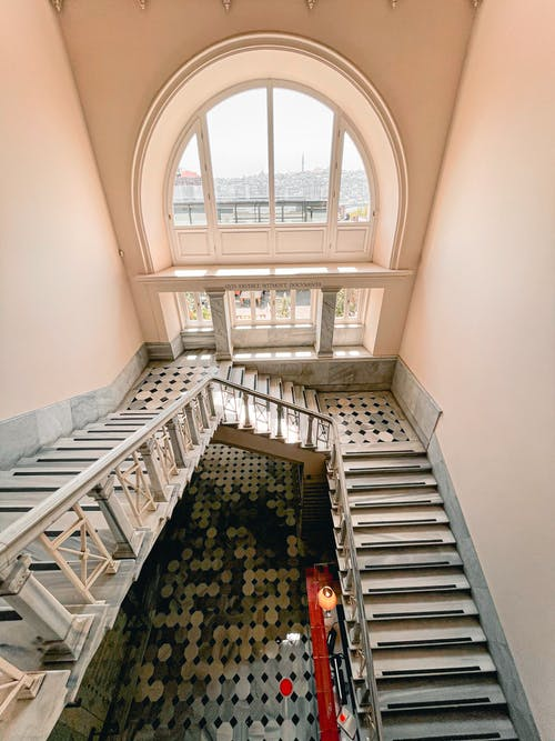 High angle of stone stairway with railing inside of old building with classic design and arched window