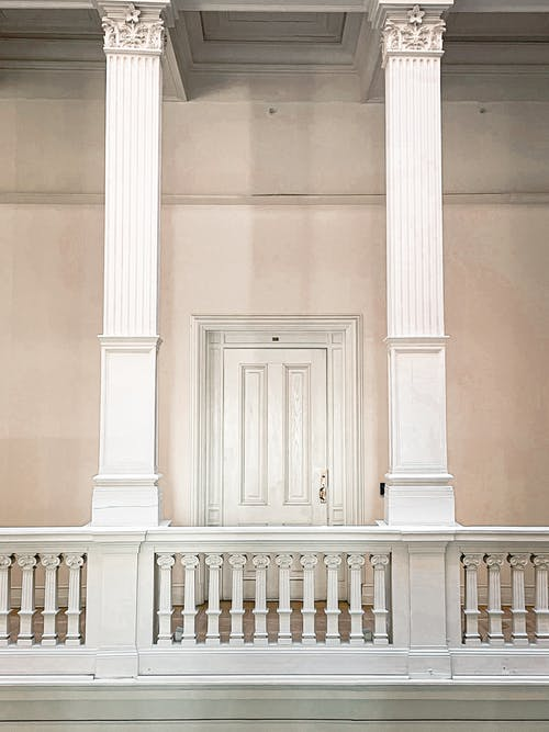 White pillars and railing on gallery with white doorway in classic interior of old building