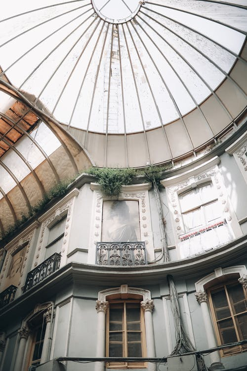 Low angle of old building passage with windows in inner patio under glass dome in daylight