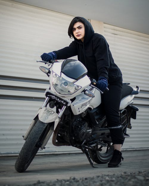 A Woman in Black Hoodie Riding a Motorcycle