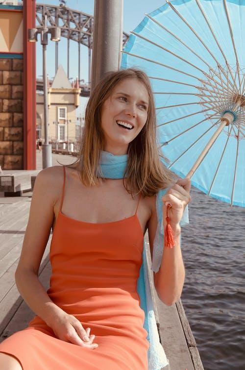 Woman in Orange Spaghetti Strap Top Holding Umbrella