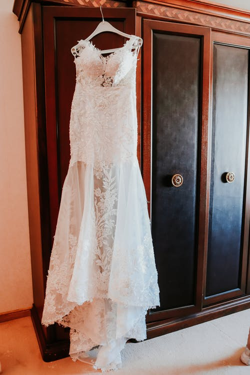 Elegant white lace bridal dress hanging on wooden closet in room before wedding ceremony