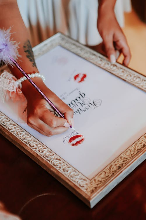 Crop lady writing on framed picture during bridal shower