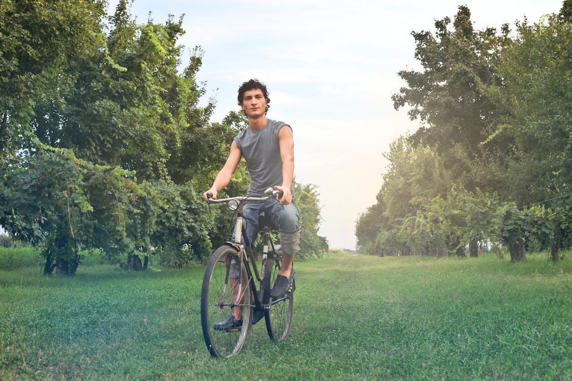 Man in Gray Sleeveless Shirt Riding Bike