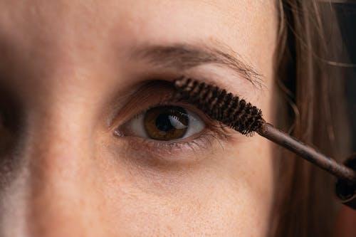 A Close-Up Shot of a Person Applying a Mascara Makeup