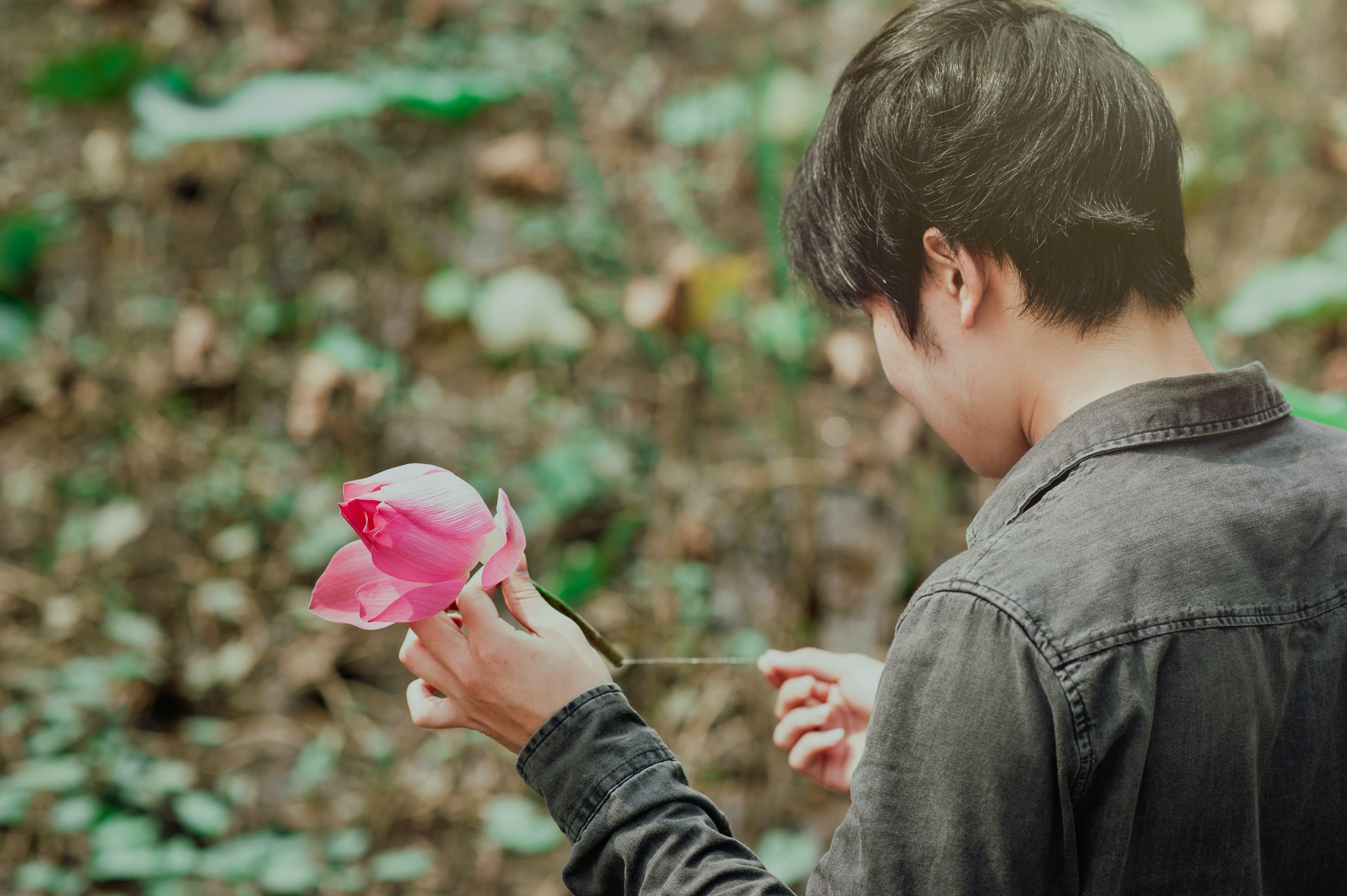 Man in Black Denim Jean Holding Pink Flower