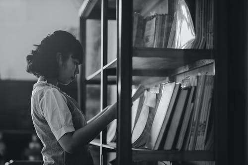 Grayscale Photo of a Woman Holding a Book Inside the Library