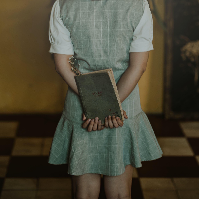 Woman Wearing Grey Dress Holding Book