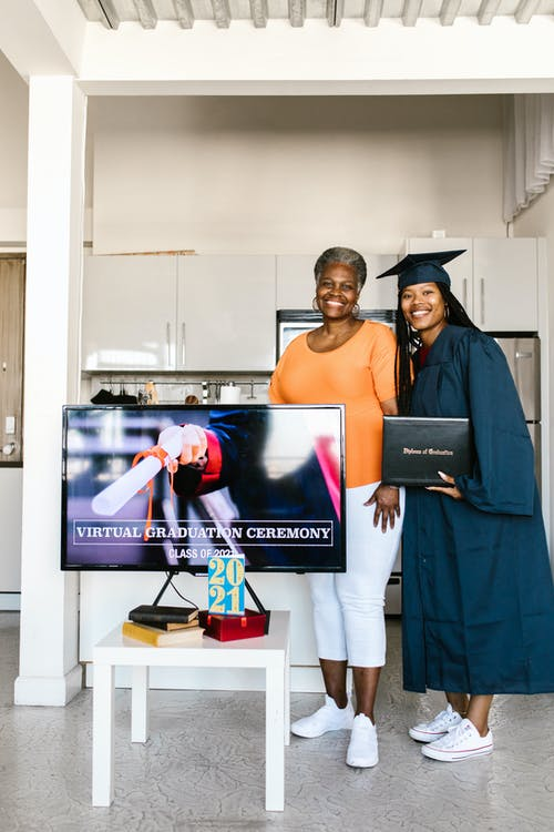 Woman and Her Daughter in Graduation Gown Smiling and Posing for the Photo
