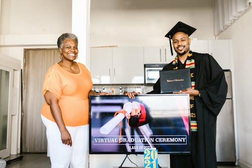 Man Wearing Graduation Toga Having Picture Taken Together With His Mother