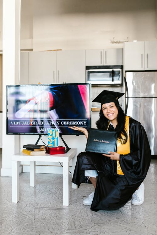 Woman in Academic Dress Holding Her Diploma and Posing Near Big TV Screen
