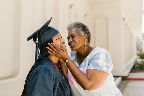 Proud Mother Kissing Her Daughter At Graduation