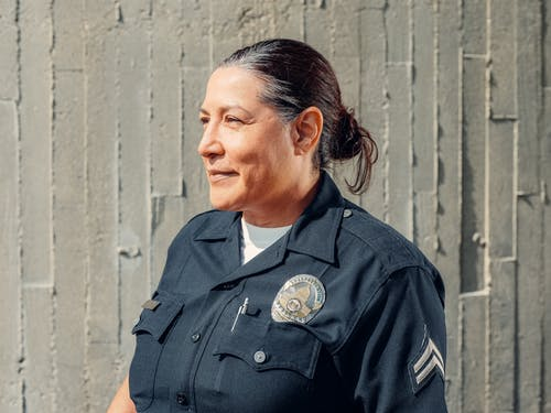 Man in Black Police Uniform Standing Beside Gray Wall