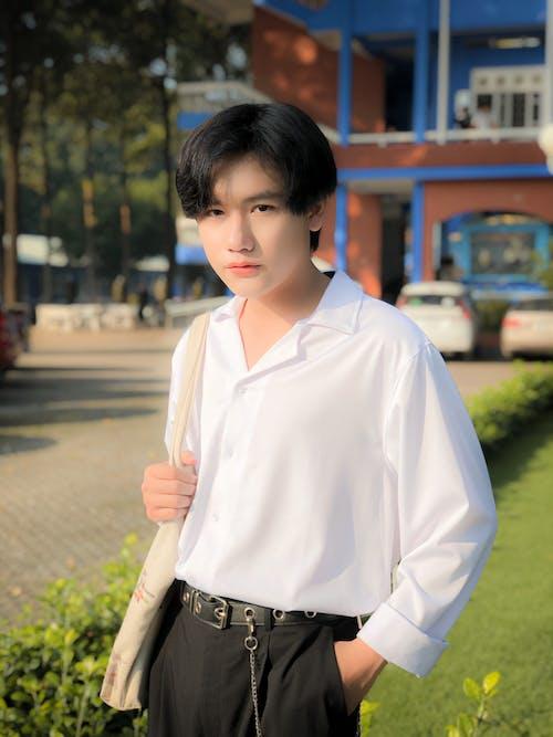 Man in White Dress Shirt and Black Pants Standing on Sidewalk