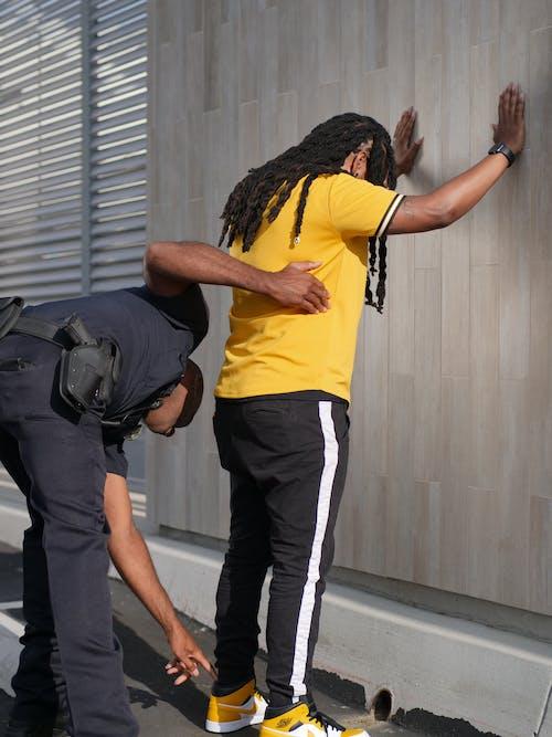 Hombre De Camiseta Amarilla Y Pantalón Negro De Pie Junto A La Pared Gris