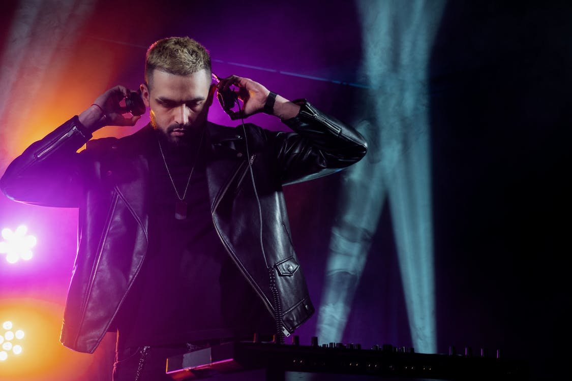 Self assured young bearded male DJ in trendy leather jacket adjusting headphones while performing music on stage in dark illuminated nightclub