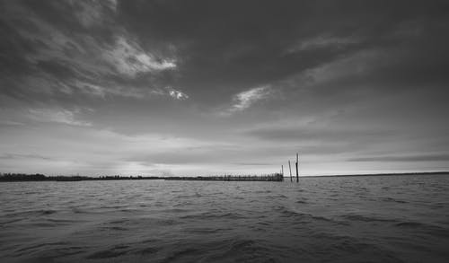 Grayscale Photo of Sea Under Cloudy Sky