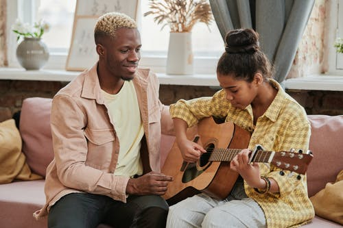 Girl in a Yellow Shirt Learning How to Play the Guitar Next to Her Tutor