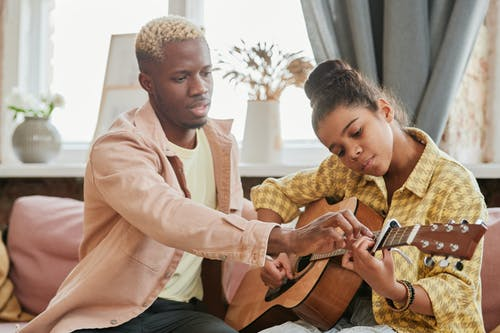Безкоштовне стокове фото на тему «акустична гітара, афроамериканський, Вибірковий фокус»