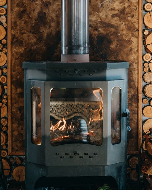 Orange flame of vintage metal burning fireplace placed near wooden wall in cozy house