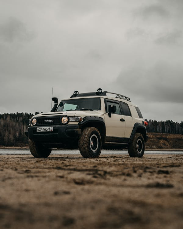 White and Black Jeep Wrangler on Brown Field