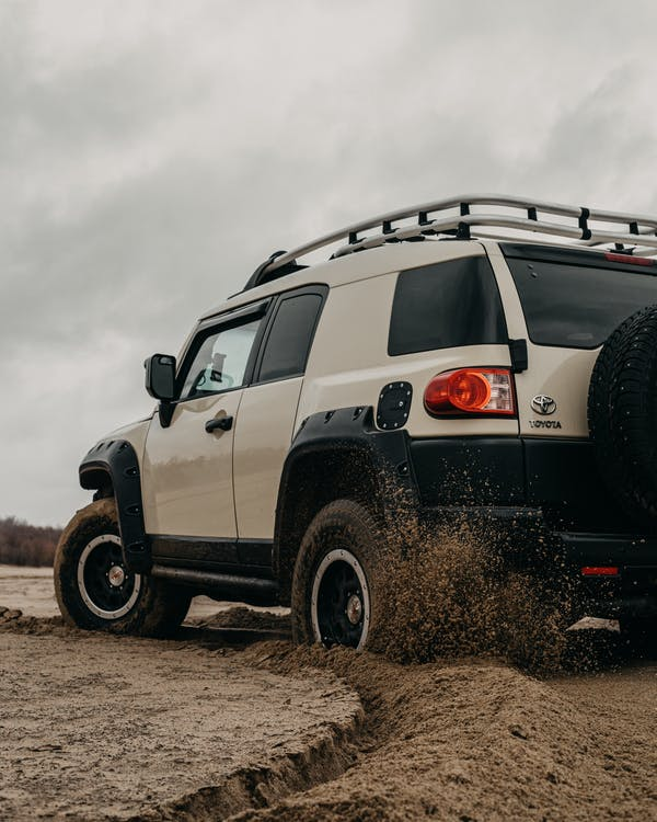 White and Black Jeep Wrangler on Brown Field Under White Cloudy Sky