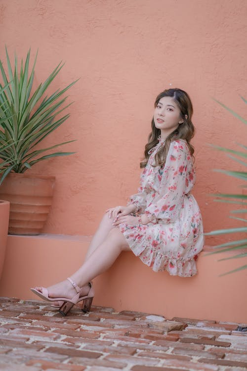 Woman in Pink and White Floral Long Sleeve Dress Sitting on Brown Concrete Bench