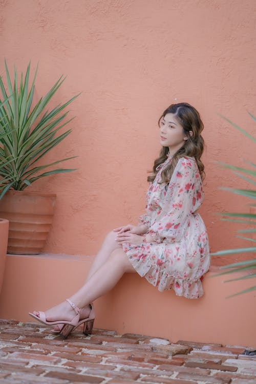 Woman in White and Pink Floral Dress Sitting on Brown Concrete Wall
