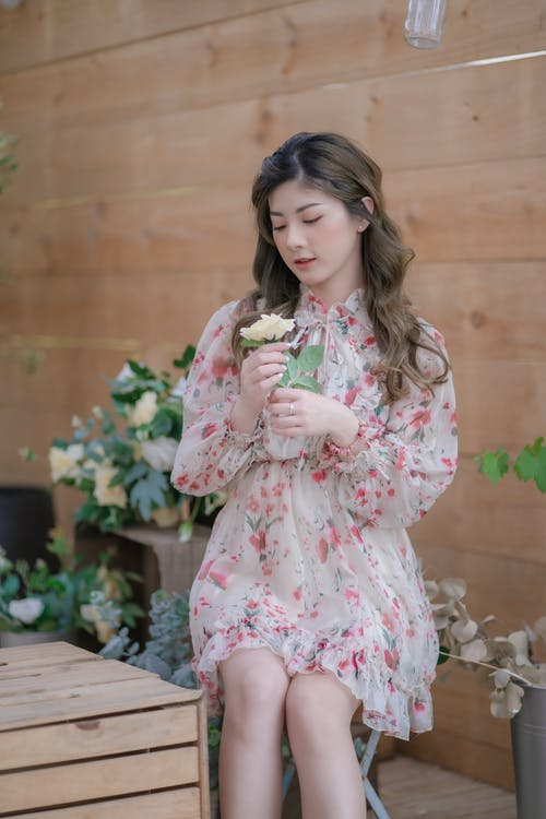 Girl in Pink and White Floral Dress Holding Pink Flowers