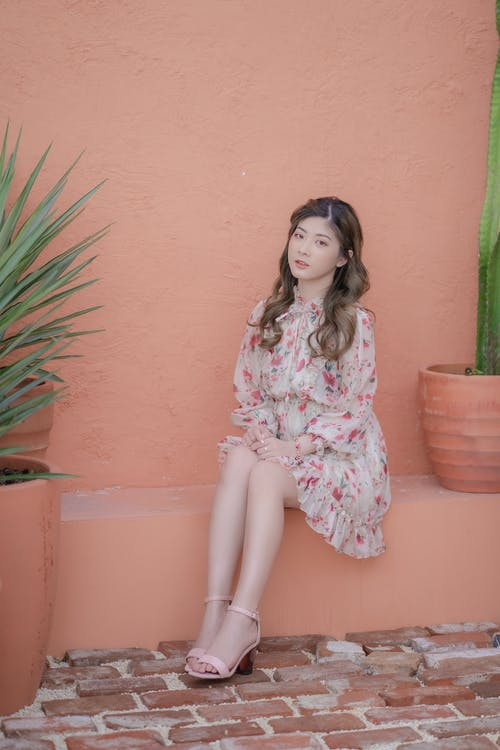 Woman in White and Pink Floral Dress Sitting on Brown Concrete Bench