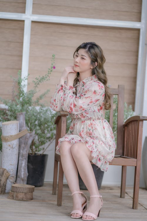 Woman in Pink and White Floral Dress Sitting on Brown Wooden Chair