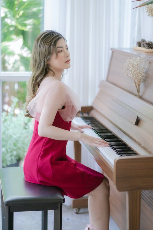 Woman in Red Dress Playing Piano