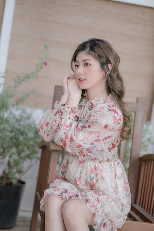 Girl in White and Pink Floral Dress Sitting on Brown Wooden Chair