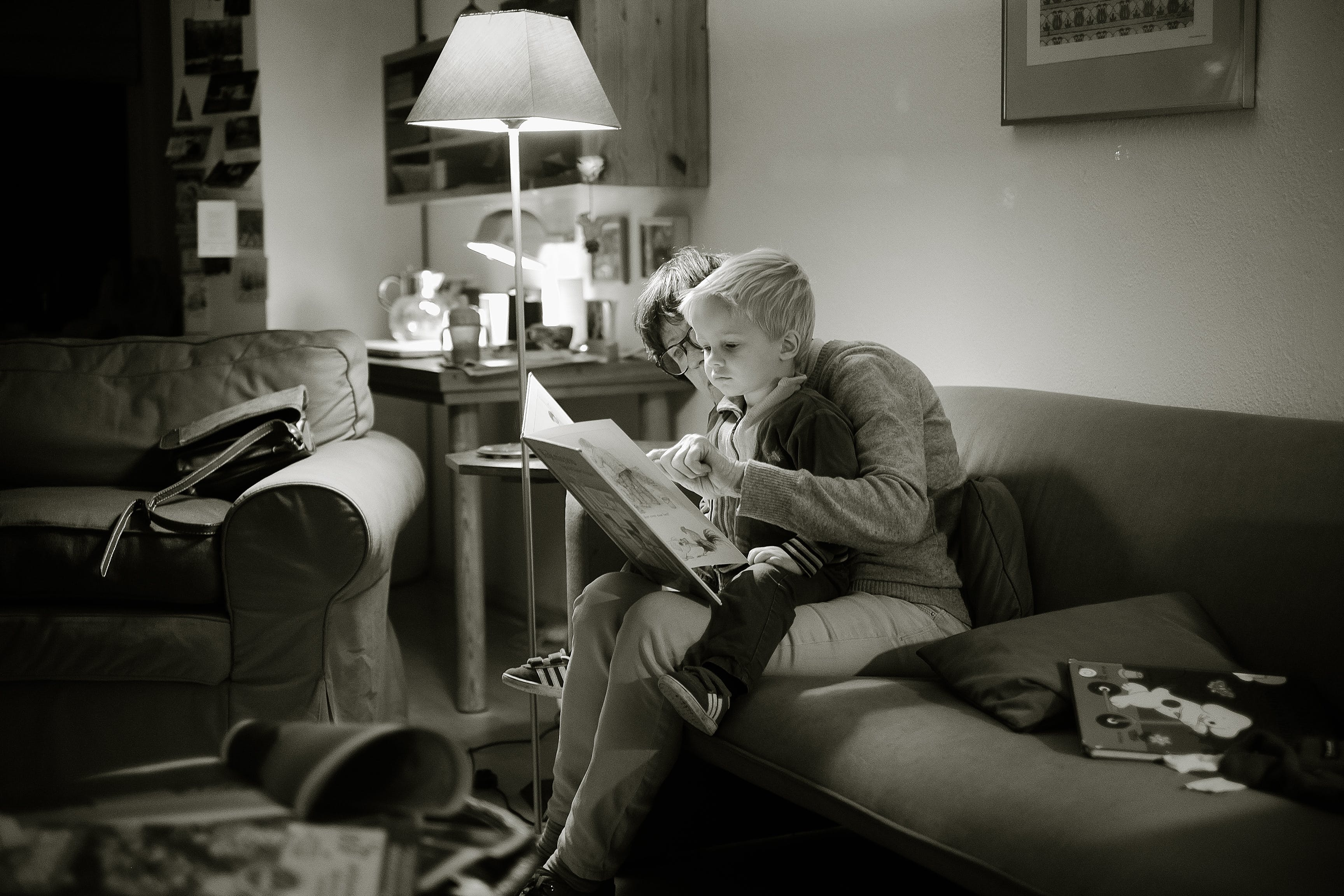 Grayscale Photography of Child on Lap of Woman While Reading Book