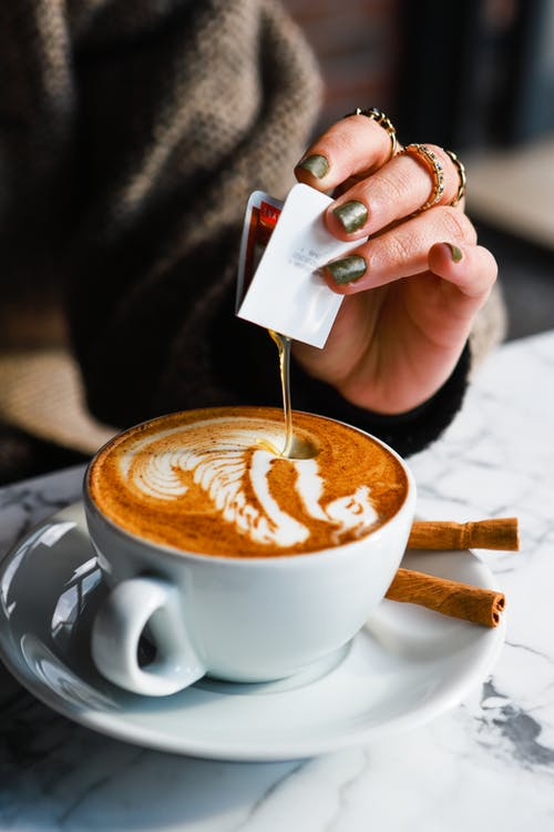Photo of a Person's Hand Pouring Syrup on a Cappuccino