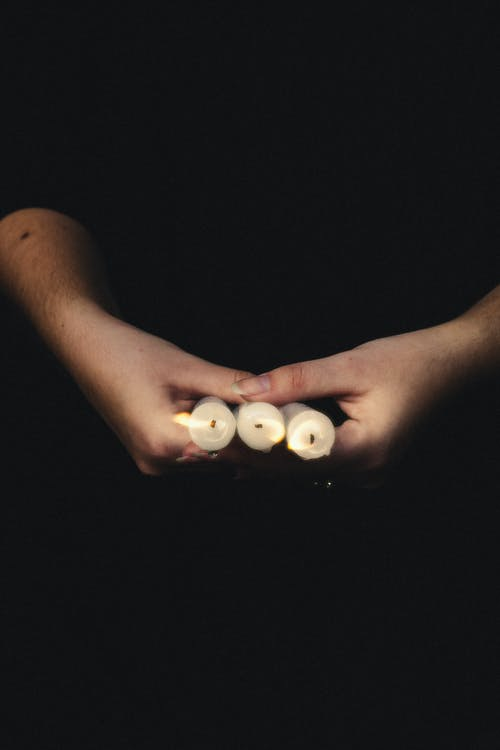 A Person Holding Lighted Candles
