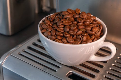 Close-Up Photo of Roasted Coffee Beans in a White Cup