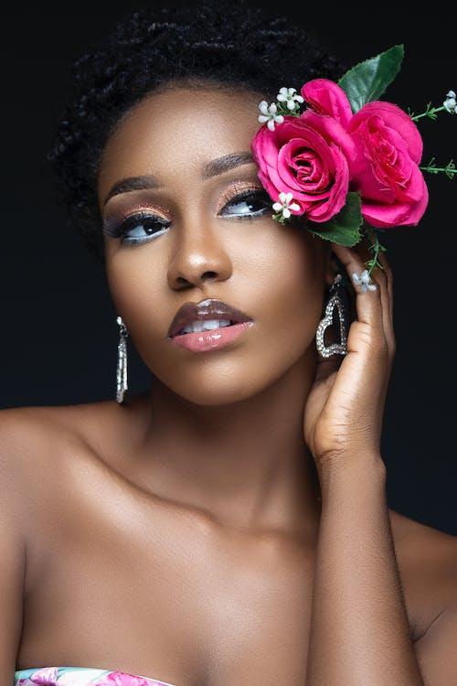 Elegant black woman with glamorous makeup and rose