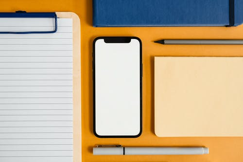 A Flatlay of a Smartphone and Office Supplies