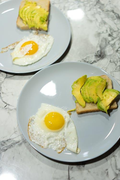 Яйцо солнечной стороной вверх на белой керамической тарелке