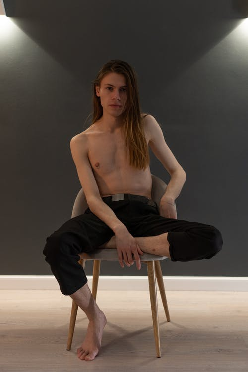 A Topless Man Sitting on a Chair