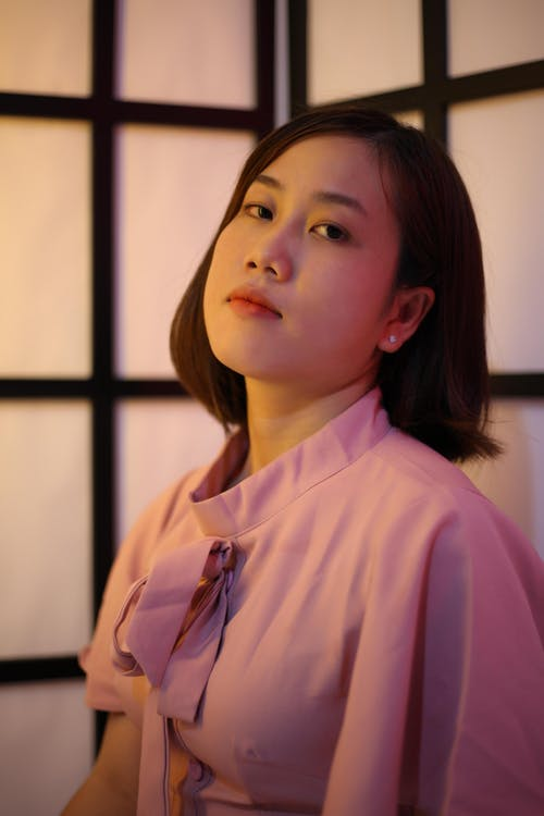 Asian woman with short hair in elegant pink blouse
