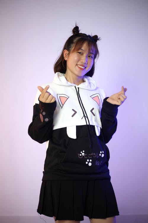 Cheerful Asian woman in casual trendy hoodie and skirt