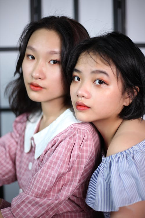 Tender ethnic teenagers with red lips and dark hair looking at camera on blurred background