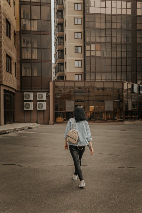 Back view of anonymous female in trendy clothes and with backpack walking on street in urban area in city