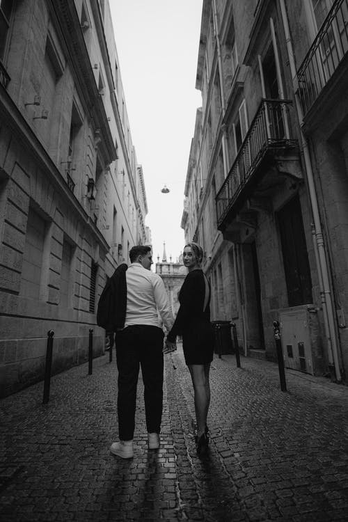Man and Woman Walking on Street in Grayscale Photography