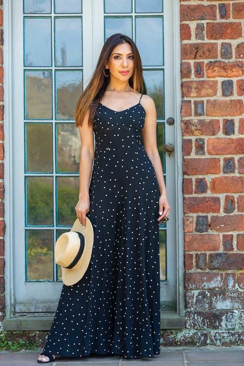 Woman in Black Sleeveless Dress Standing Beside Window