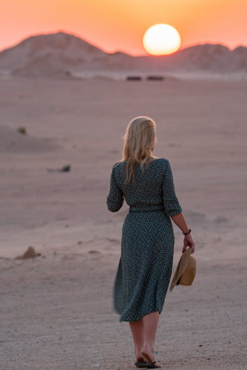 Back view full body of unrecognizable female in dress with hat in hand strolling on sandy area during trip on sunset time