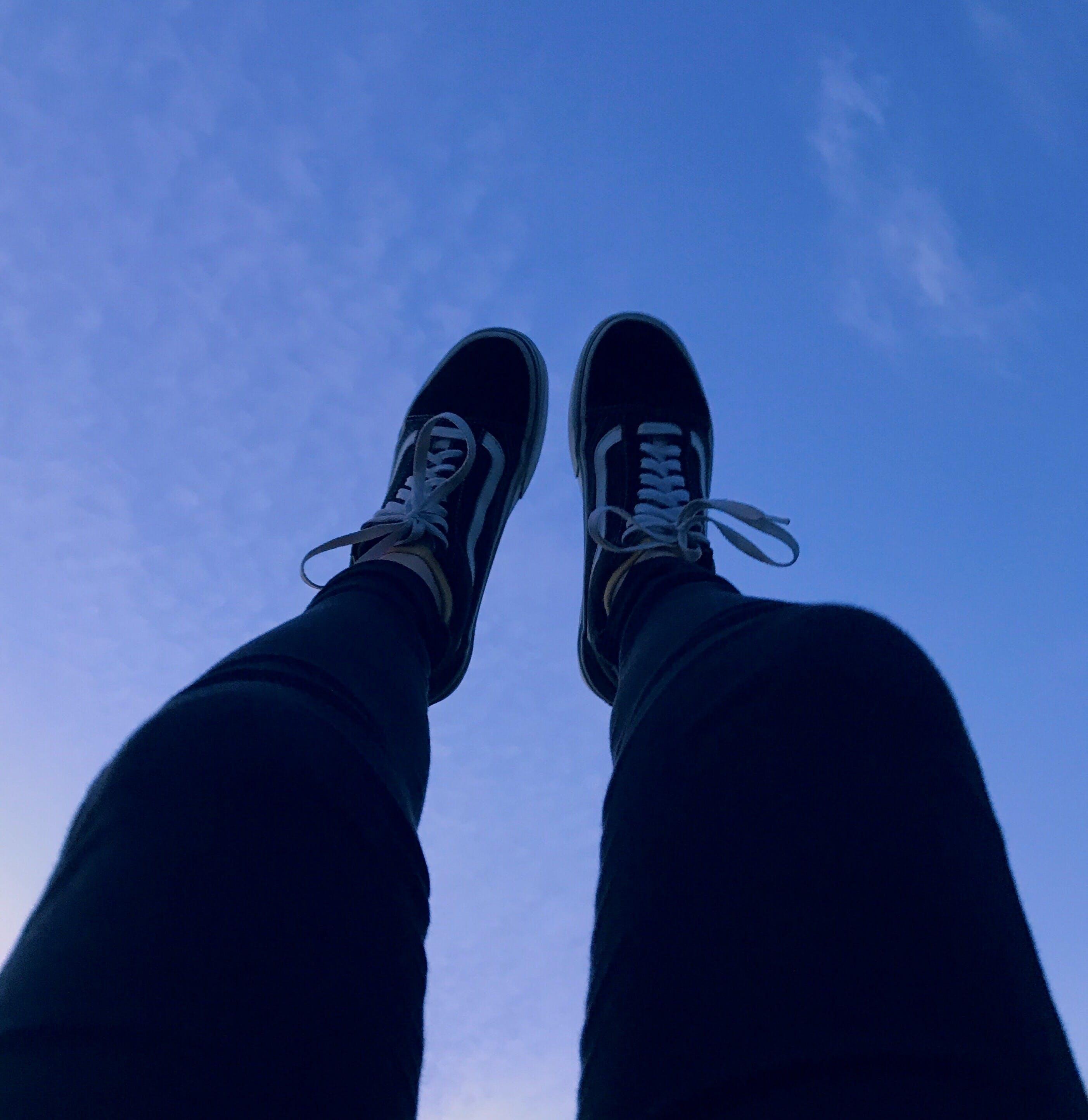 Person Wearing Vans Old Skool Sneakers Raising His Feet Pointing to They Sky