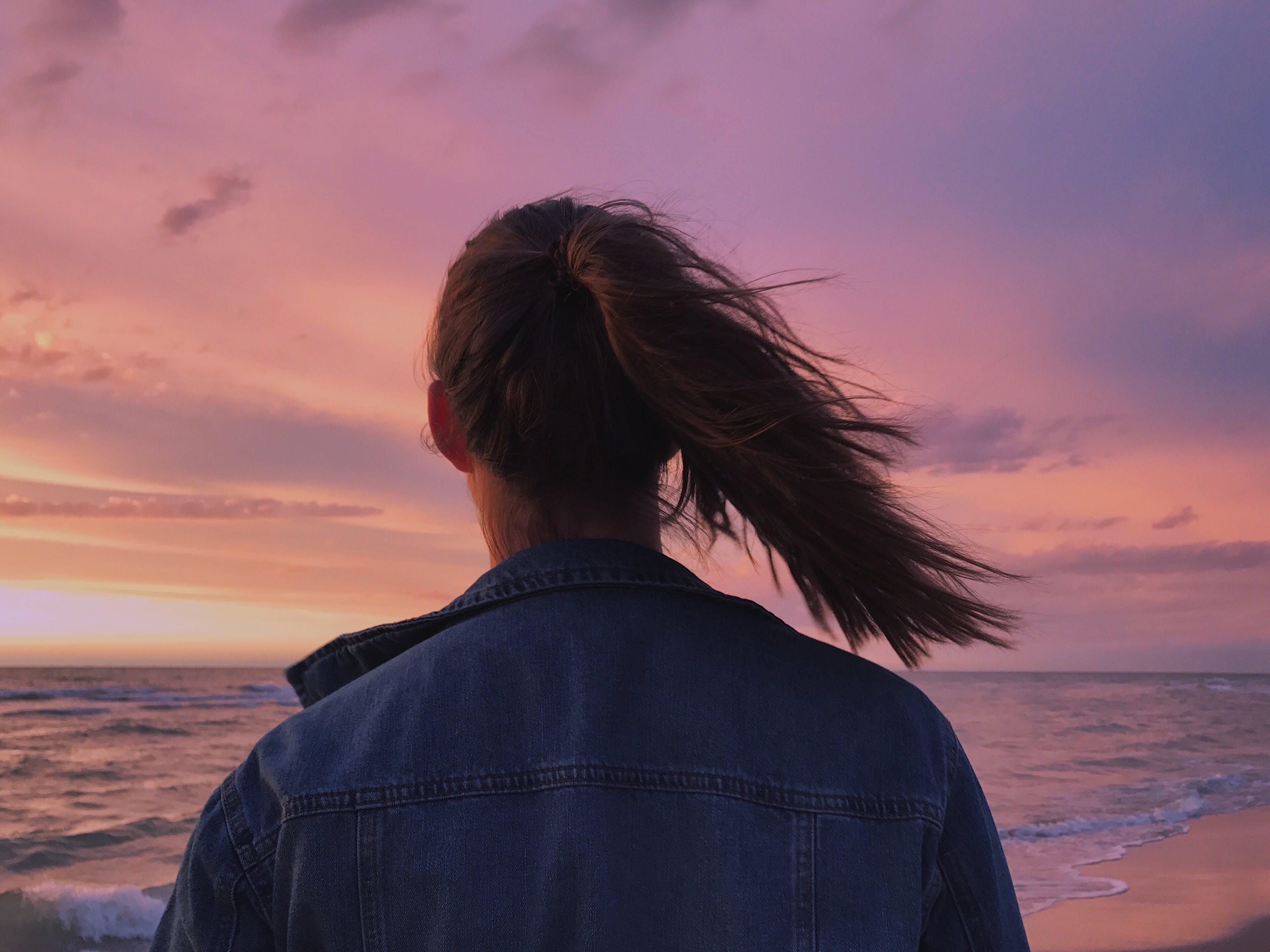 Woman Wearing Blue Denim Jacket Looking At The Beach